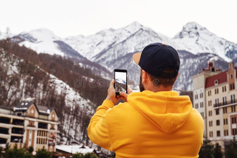 r 黄色有冠乌鸦和盖帽立场的有胡子的男性游人在高多雪的山背景,在智能手机做照片 库存照片