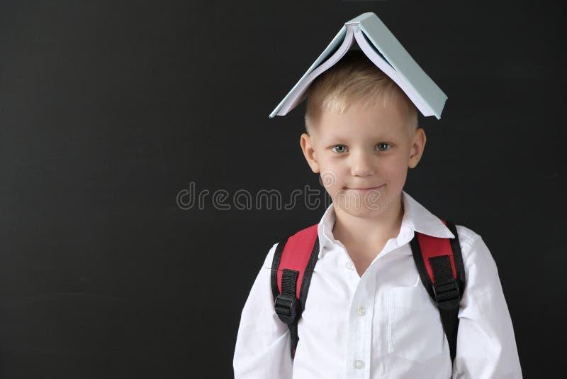 r 黑板的滑稽的小男孩 从小学的孩子有在他的头的书的 r 库存照片