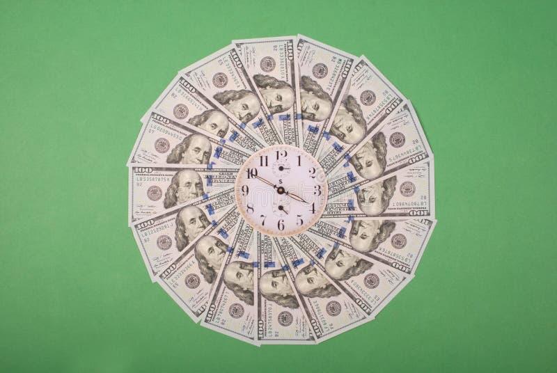 时钟和美元的概念 曼荼罗万花筒上的钟 抽象货币背景光栅图案重复曼陀罗 库存图片