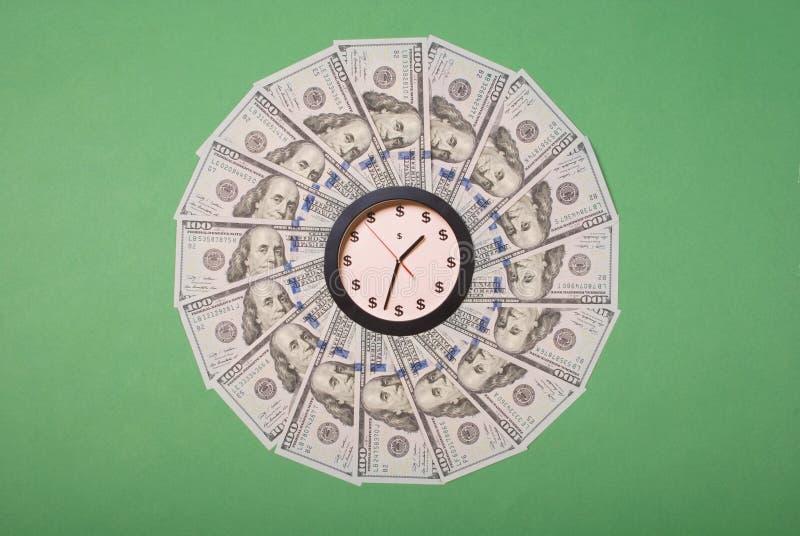 时钟和美元的概念 曼荼罗万花筒上的钟 抽象货币背景光栅图案重复曼陀罗 免版税库存照片