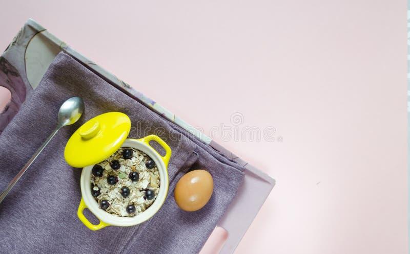 r 舱内甲板在一个黄色罐、鸡蛋、muesli用新鲜的蓝莓和无核小葡萄干的一个盘子燕麦粥放置在一块紫色餐巾 图库摄影