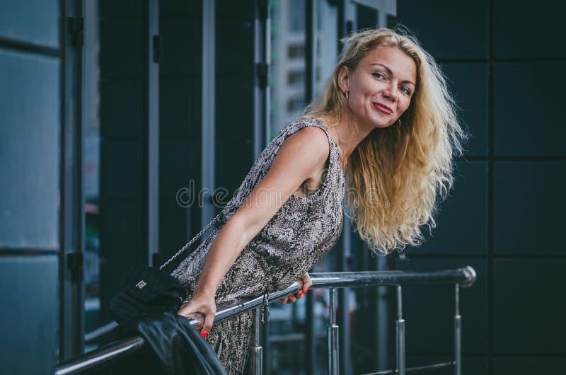 r 有壮观的头发的一名美丽的高亭亭玉立的白肤金发的妇女在有爬行动物印刷品蛇的一件时髦长的礼服紧贴 免版税库存图片