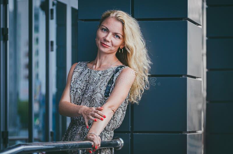 r 有壮观的头发的一名美丽的高亭亭玉立的白肤金发的妇女在有爬行动物印刷品蛇的一件时髦长的礼服紧贴 库存图片