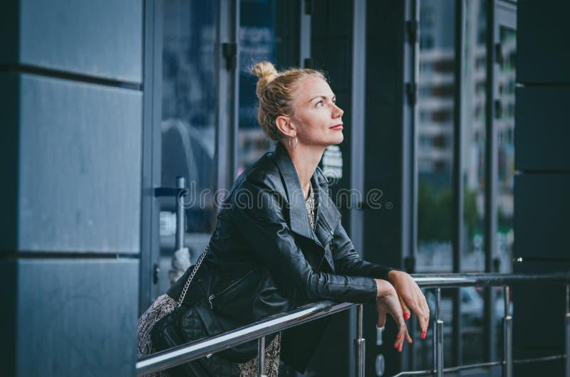 r 有被会集的头发的一名美丽的高,苗条白肤金发的妇女在一件时髦长的礼服的一个小圆面包有爬行动物蛇的 库存照片