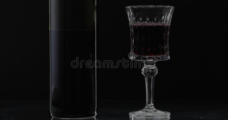 R??any wino Czerwone wino w wina szkle z butelką nad czarnym tłem sylwetka obrazy royalty free