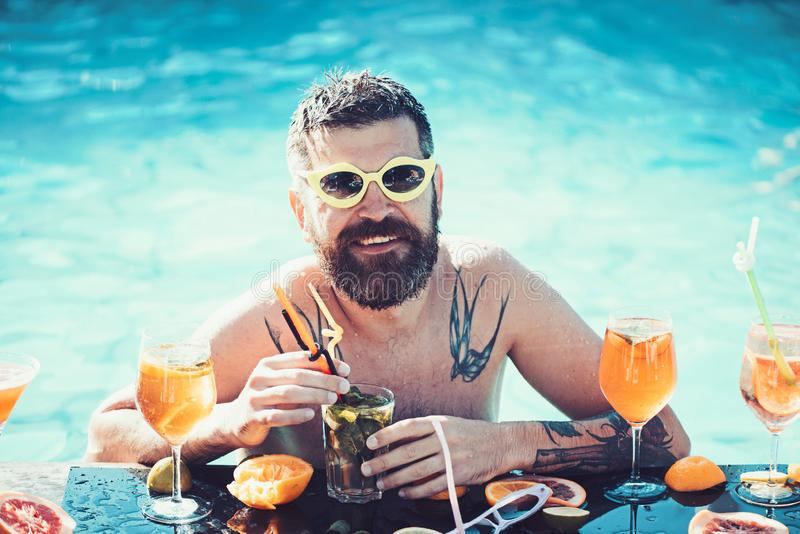 R?ception au bord de la piscine, vitamine et suivre un r?gime Cocktail avec le fruit ? l'homme barbu dans la piscine Natation d'h image libre de droits