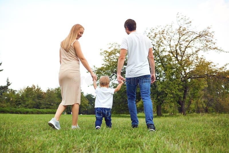 R?ckseitige Ansicht Familie mit einem Kind geht in den Park stockfoto