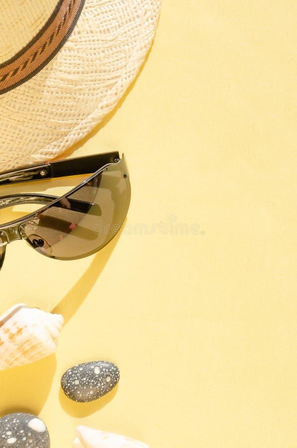 r Conception ?tendue plate de chapeau de paille, de lunettes de soleil et de coquillages sur le fond jaune photographie stock libre de droits