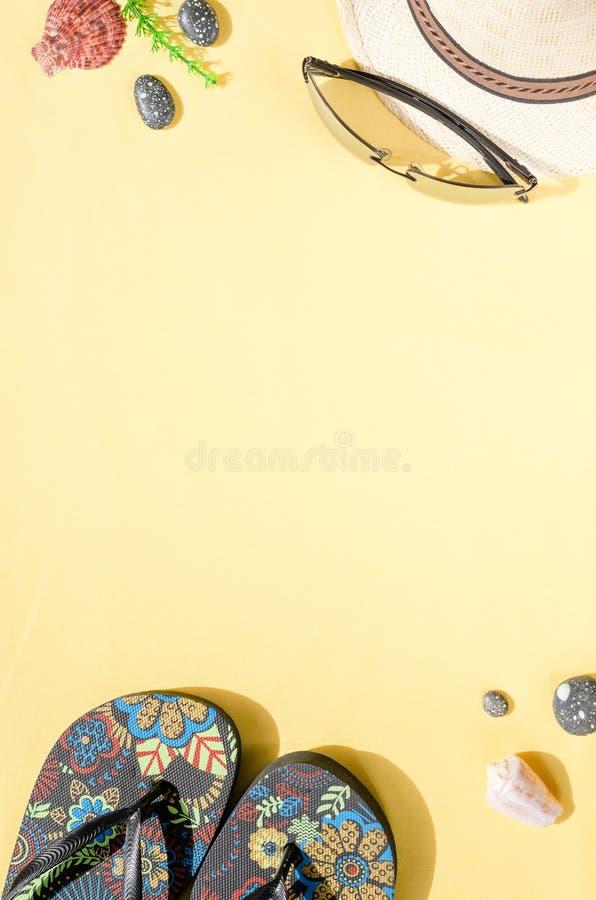 r Configuration plate de chapeau de paille, de lunettes de soleil, de bascules ?lectroniques et de coquillages sur le fond jaune images libres de droits