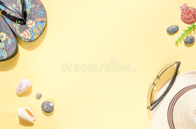 r Configuration plate de chapeau de paille, de lunettes de soleil, de bascules ?lectroniques et de coquillages sur le fond jaune image libre de droits
