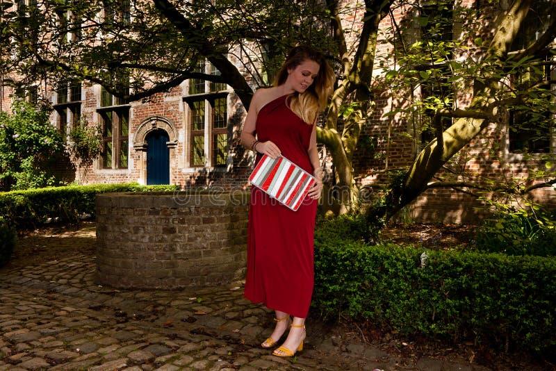 R?d antik kl?nning f?r kvinna, Groot Begijnhof, Leuven, Belgien fotografering för bildbyråer