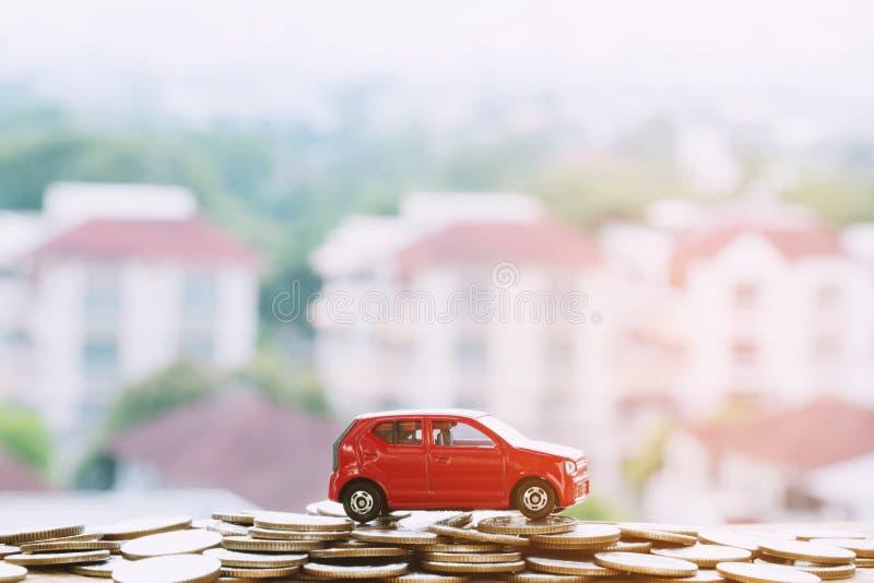R?d bil f?r liten leksak ?ver mycket pengar staplade mynt f?r bankl?nkostnadsfinans royaltyfria bilder