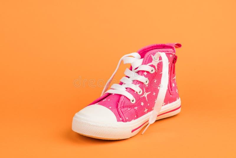 Röd children& x27; s-skor På orange bakgrund royaltyfria foton