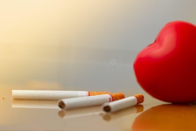 R?d hj?rta och cigaretter R?ka f?rst?rande h?lsa f?r cigarett Hj?rtsjukdom royaltyfria bilder