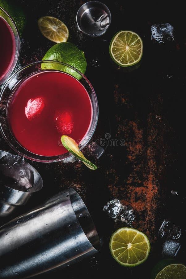 R?d kosmopolitisk coctail med limefrukt royaltyfri bild