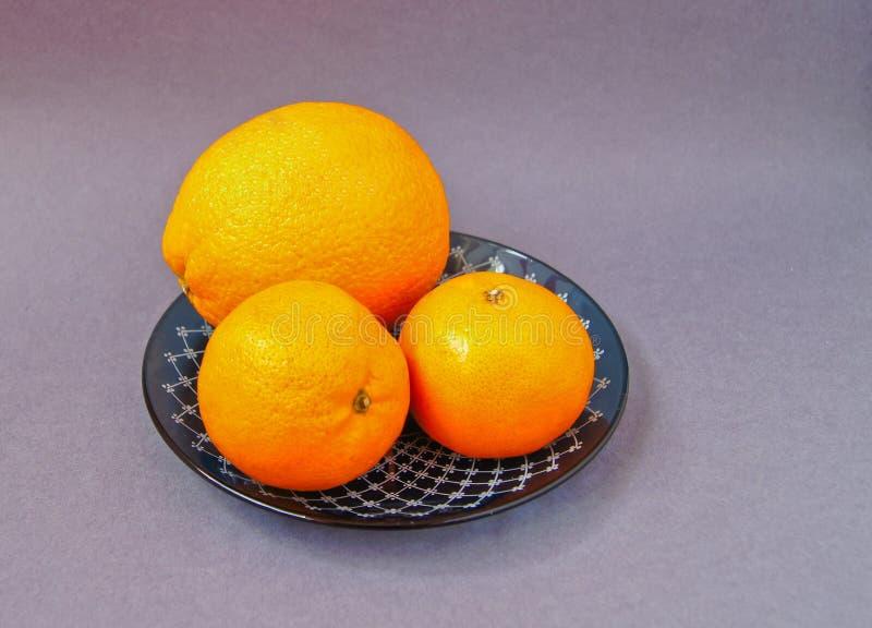 R?d platta med apelsiner och den gr?na sidaflaskan f?r tangerin med fruktsaft p? ljus bakgrund Kopieringsutrymme f?r b?sta sikt royaltyfri bild
