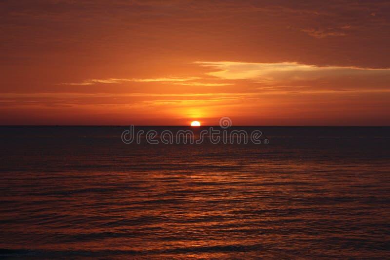 R?d solnedg?ng ?ver havet fotografering för bildbyråer