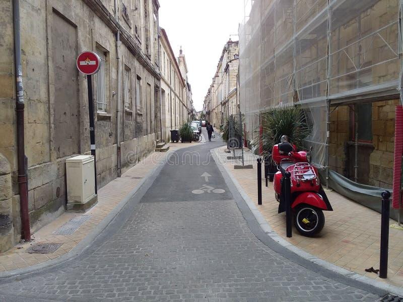 R?d tappningsparkcykel som parkeras p? trottoaren av den tomma stadsgatan royaltyfri bild
