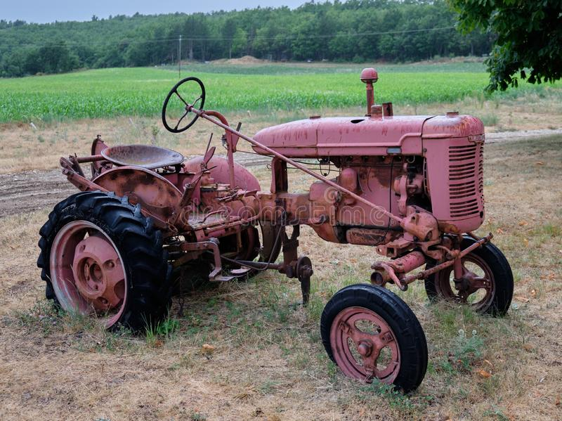 R?d traktor i ett f?lt arkivfoto