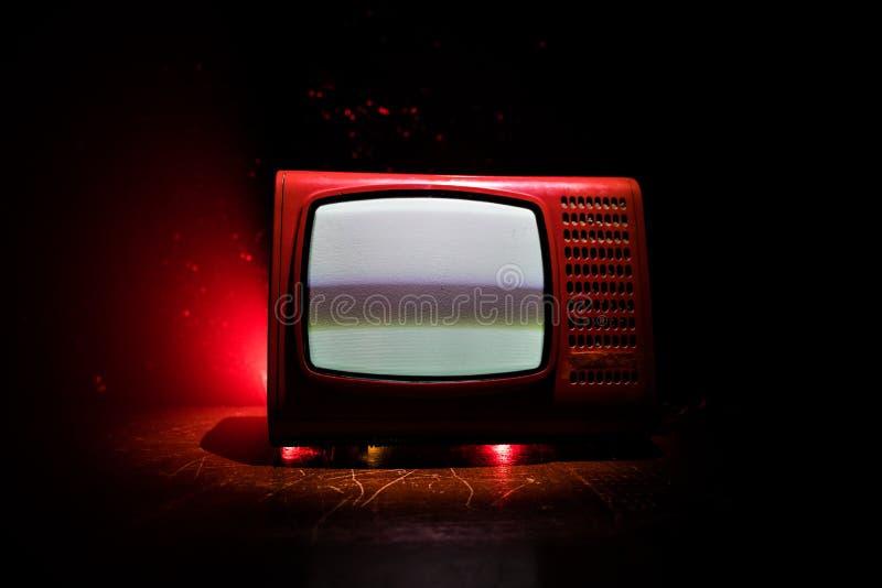 R?d TV f?r gammal tappning med vitt ov?sen p? m?rk tonad dimmig bakgrund Retro gammal televisionmottagare ingen signal arkivbild