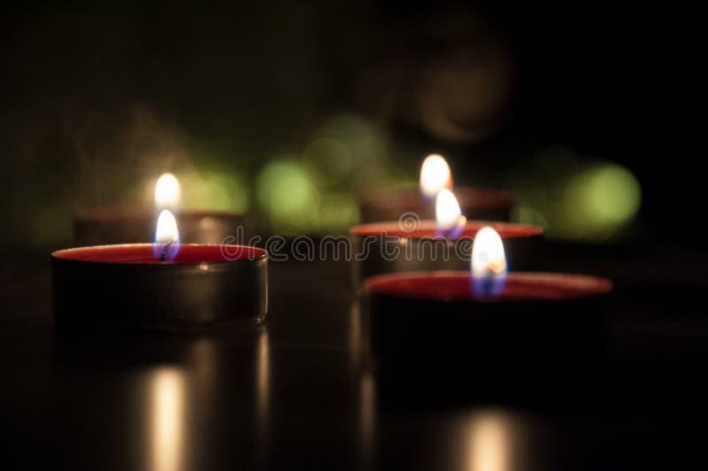 R?da stearinljus som gl?der i natten arkivbilder
