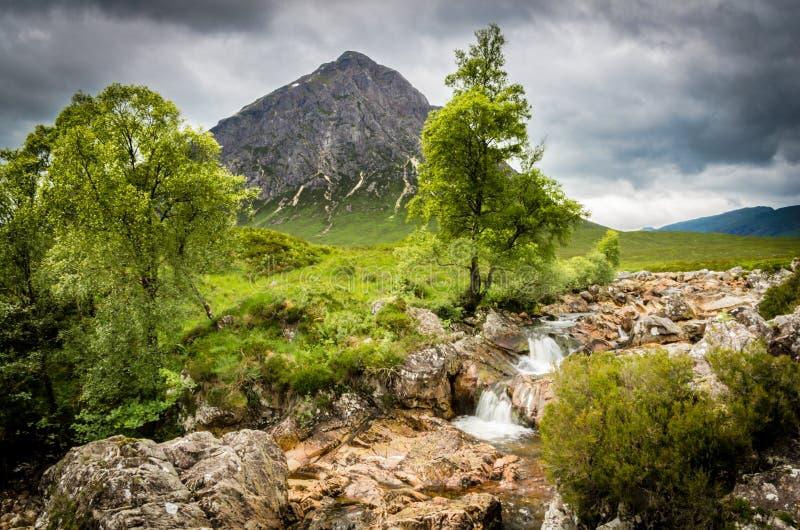 ² r de Buachaille Etive MÃ da montanha e cachoeira rochosa em Escócia foto de stock