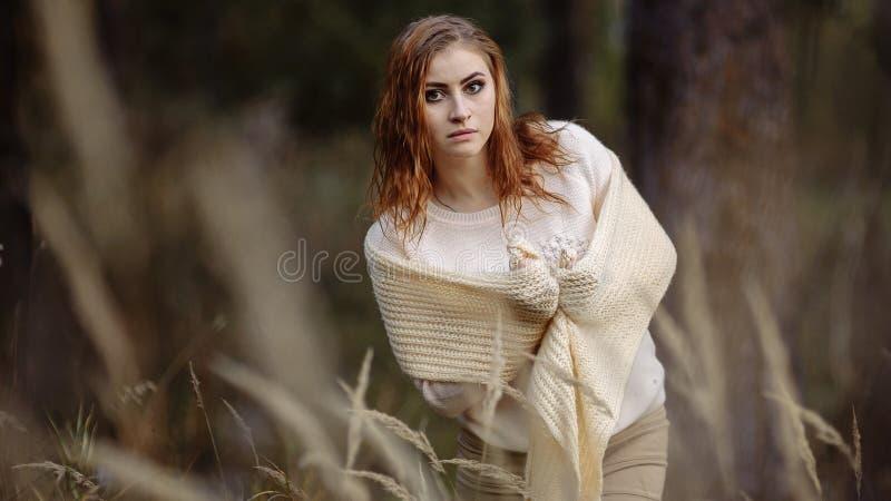 R?dh?rig flicka i ljus kl?der mot bakgrunden av h?stskogen och gula ?ron royaltyfria bilder