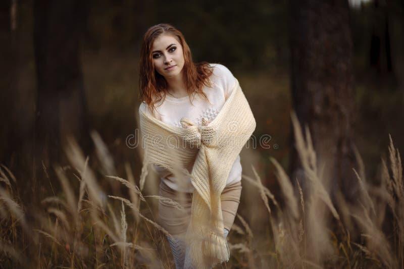 R?dh?rig flicka i ljus kl?der mot bakgrunden av h?stskogen och gula ?ron arkivbild