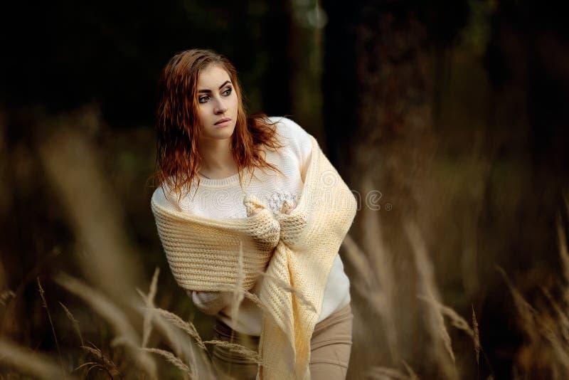 R?dh?rig flicka i ljus kl?der mot bakgrunden av h?stskogen och gula ?ron arkivfoto