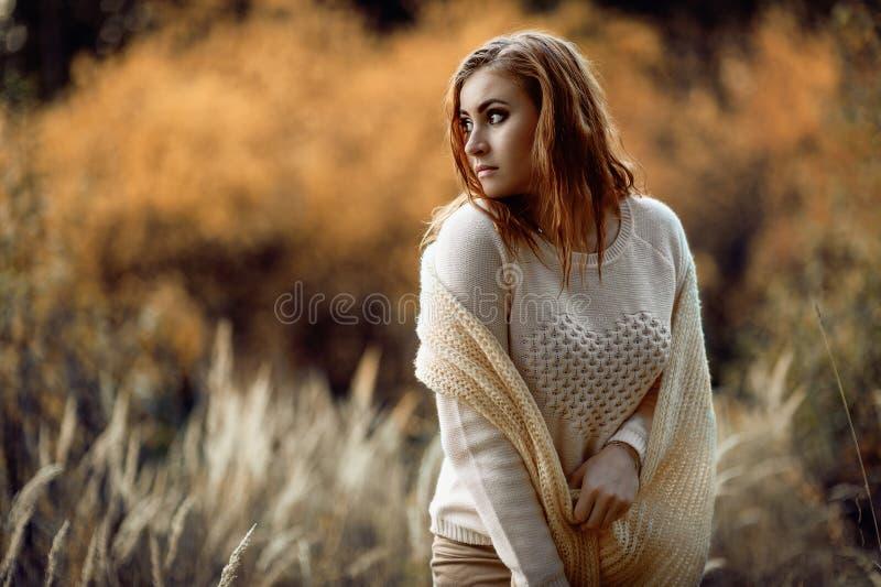 R?dh?rig flicka i ljus kl?der mot bakgrunden av h?stskogen och gula ?ron fotografering för bildbyråer