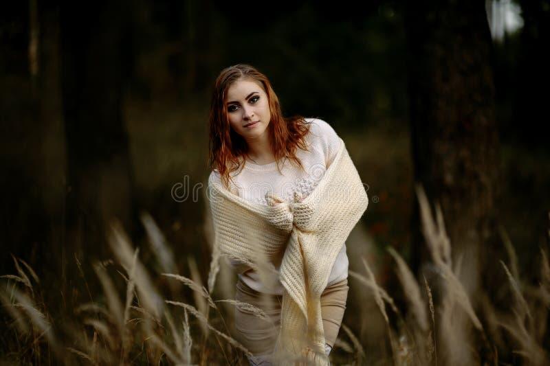 R?dh?rig flicka i ljus kl?der mot bakgrunden av h?stskogen och gula ?ron royaltyfri foto