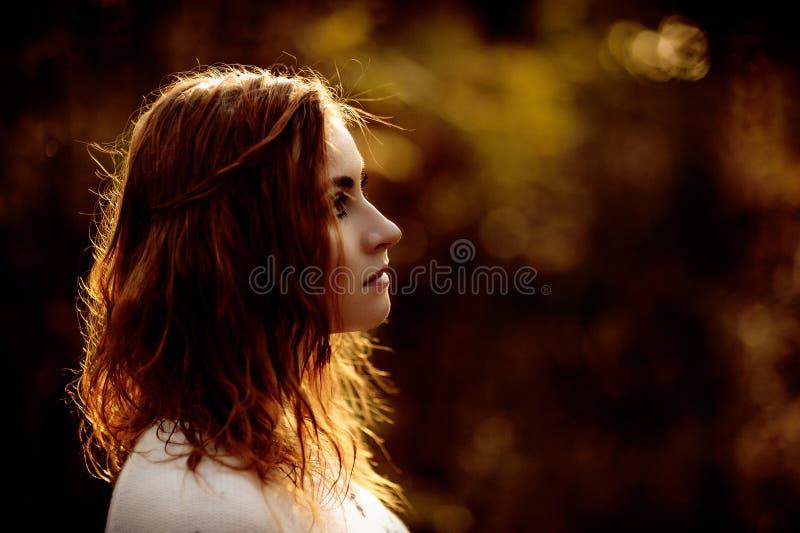 R?dh?rig flicka i ljus kl?der p? en bakgrund av h?stskogen arkivfoton