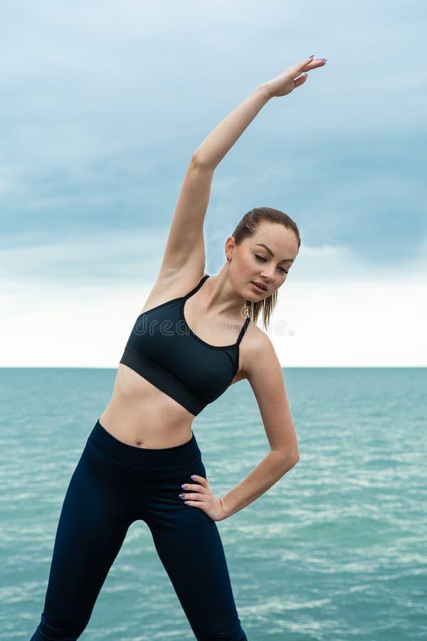 R?dh?rig, ung, idrotts- h?rlig flicka som kopplas in i gymnastik som ?r ink?rd den ?ppna luften Utf?r sport?vningar f?r arkivfoto
