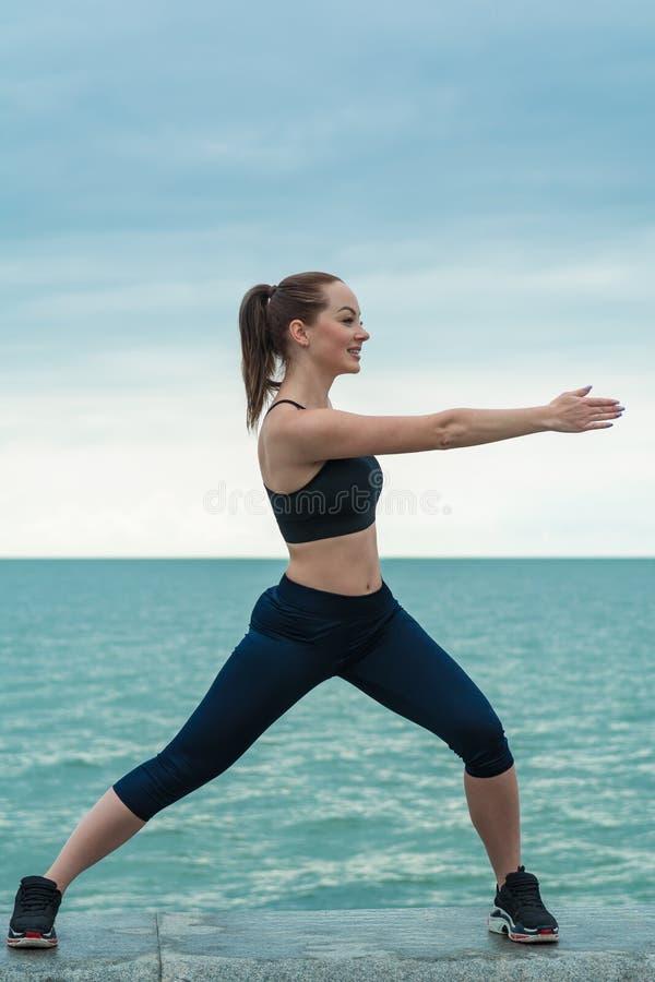 R?dh?rig, ung, idrotts- h?rlig flicka som kopplas in i gymnastik som ?r ink?rd den ?ppna luften Utf?r sport?vningar f?r royaltyfri bild