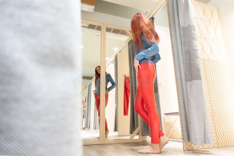 R?dh?riga r?da flickam?tt piskar fl?sanden h?rlig kvinna reflekterad i spegeln damen k?per kl?der royaltyfri foto