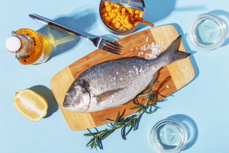 R? doradofisk p? ett tr?br?de, ingredienser f?r att laga mat och kryddor p? en bl? bakgrund royaltyfria foton