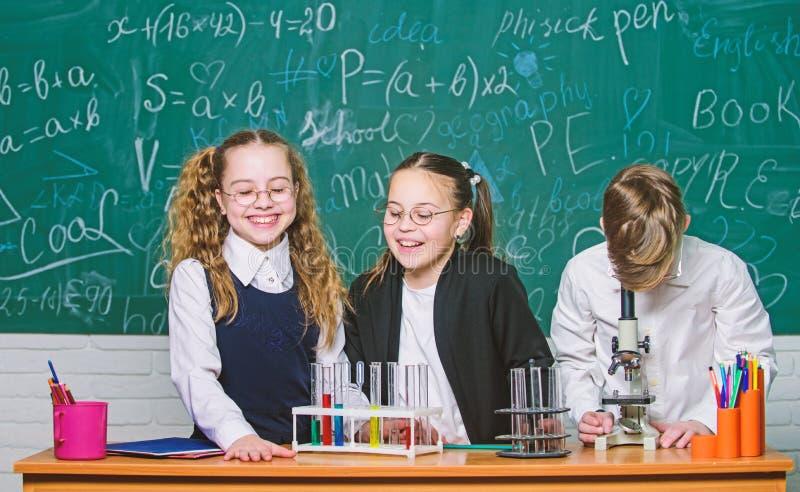 r E студенты делают эксперименты по биологии с микроскопом o стоковые фотографии rf