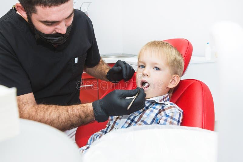 r E r 对待小男孩的牙的牙医在牙医办公室 库存照片