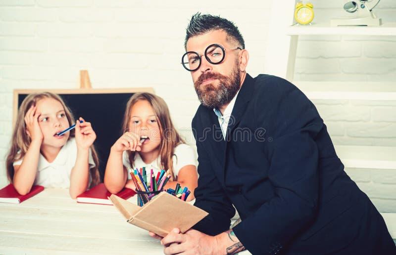 r E L'uomo dell'insegnante ha letto la storia alle ragazze che mangiano la mela immagine stock libera da diritti
