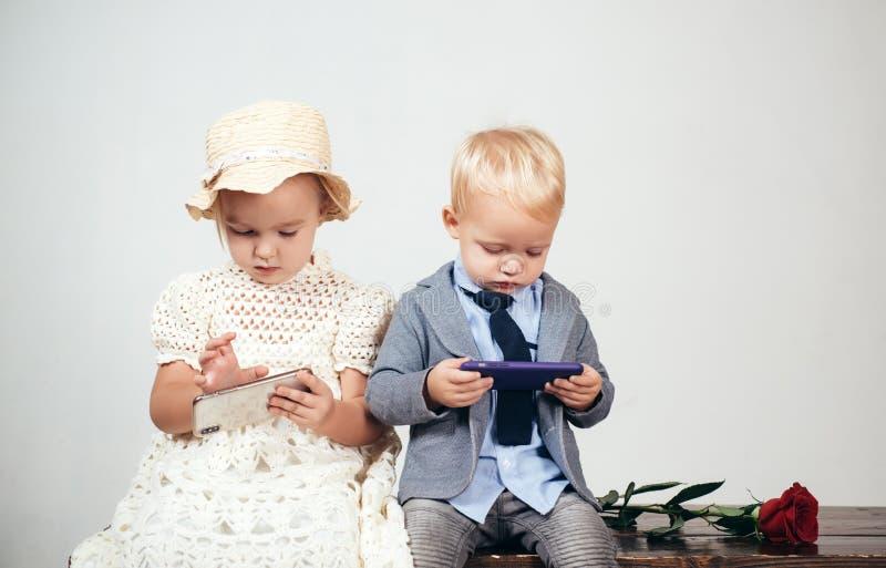 r E o 与红色玫瑰的小孩子 正式小男孩和女孩 r 免版税库存照片