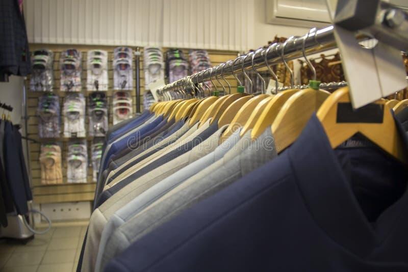 r En la suspensión en fila, se cuelgan los trajes del ` s de los hombres imagen de archivo libre de regalías