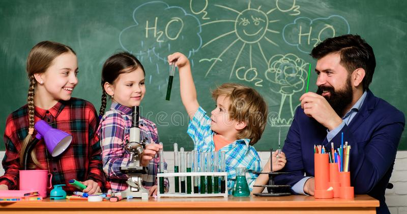r Fascinerende chemieles Mensen gebaarde leraar en leerlingen met reageerbuizen in klaslokaal royalty-vrije stock afbeeldingen