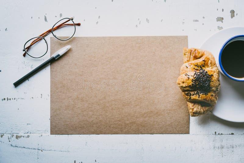 r Feuille vide de métier de maquette de papier, de stylo, de verres d'oeil et de tasse de café vides de matin photographie stock libre de droits