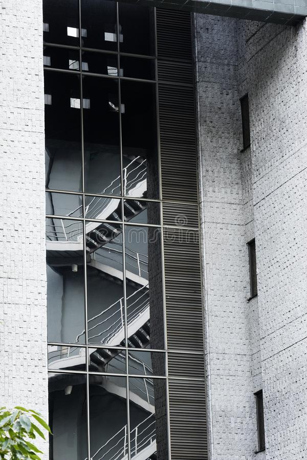 R?flexion des escaliers de secours dans le verre d'un b?timent moderne avec les murs gris de ciment photo stock