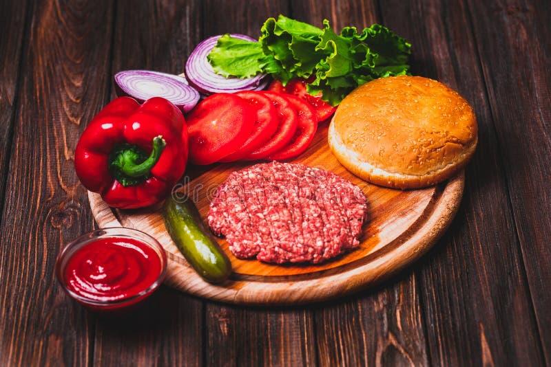 R? jordkotletter f?r biff f?r n?tk?ttk?tthamburgare med smaktillsats, ost, tomater, sallad och bullen p? tappningtr?br?den arkivbilder