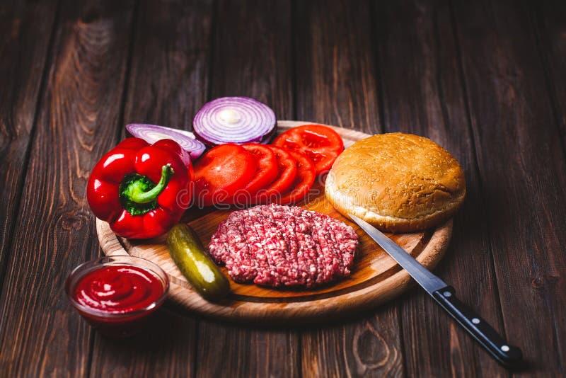 R? jordkotletter f?r biff f?r n?tk?ttk?tthamburgare med smaktillsats, ost, tomater, sallad och bullen p? tappningtr?br?den royaltyfri foto