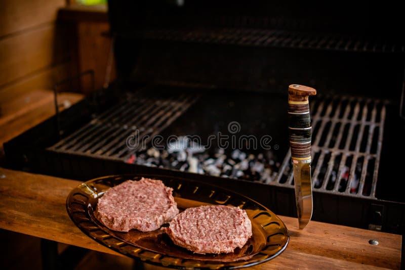 R? jordsm? pastejer f?r n?tk?ttk?tthamburgare p? papper, torkar peppar rå hamburgare för nötkött- eller grisköttköttgrillfest Sun royaltyfri foto