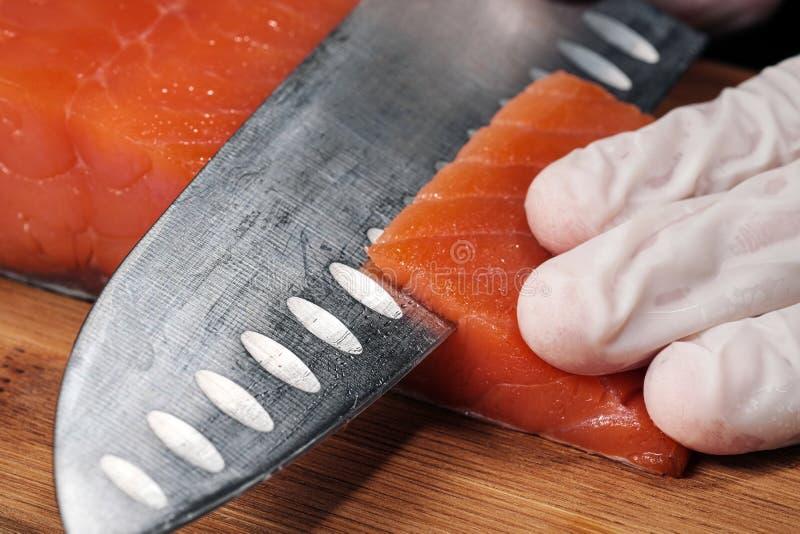 r?ka kucharz?w zako?czenie Szef kuchni ciie z nożem czerwonej ryby, uwędzony łosoś na drewnianej tnącej desce obraz royalty free