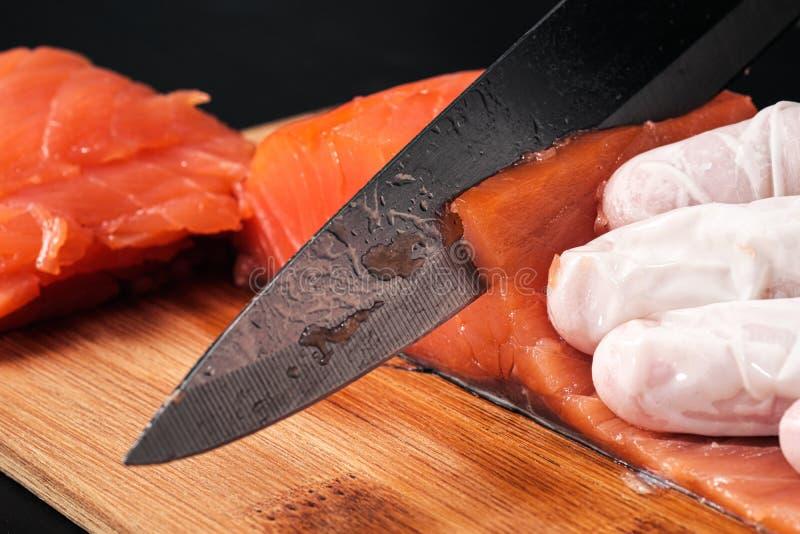 r?ka kucharz?w zako?czenie Szef kuchni ciie z nożem czerwonej ryby, uwędzony łosoś na drewnianej tnącej desce obrazy stock