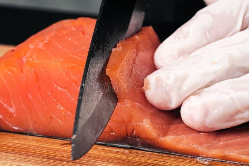 r?ka kucharz?w zako?czenie Szef kuchni ciie z nożem czerwonej ryby, uwędzony łosoś na drewnianej tnącej desce zdjęcia stock